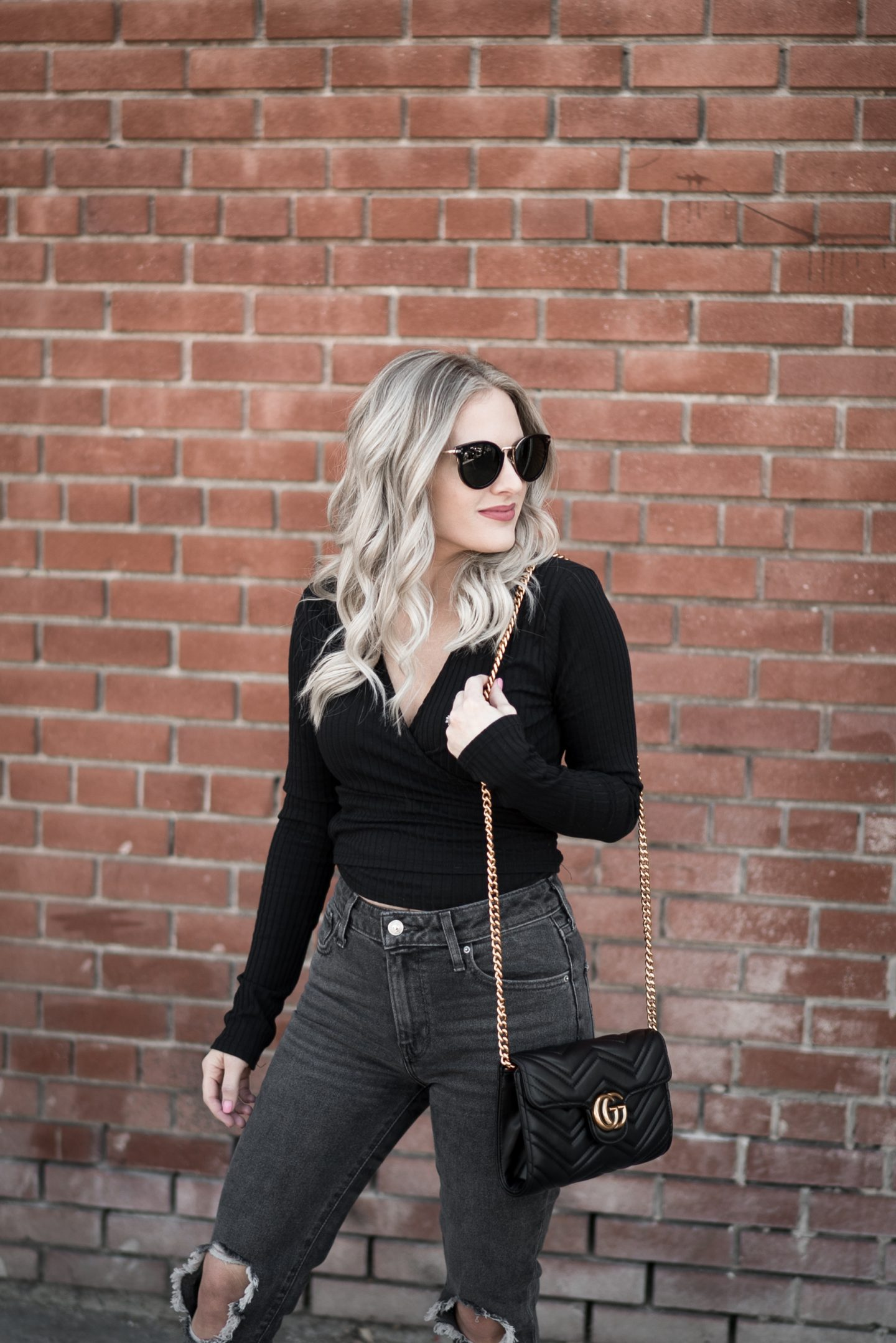wrap top all black outfit levi jeans celine sunglasses gucci bag blonde hair