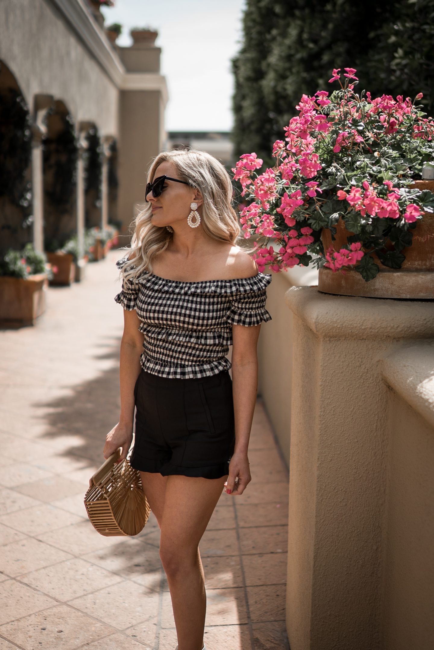Gingham Outfit featured by top US fashion blog Dress Me Blonde; Image of a woman wearing Nordstrom top, Nordstrom ruffled hem shorts and Marc Fisher white wedges.