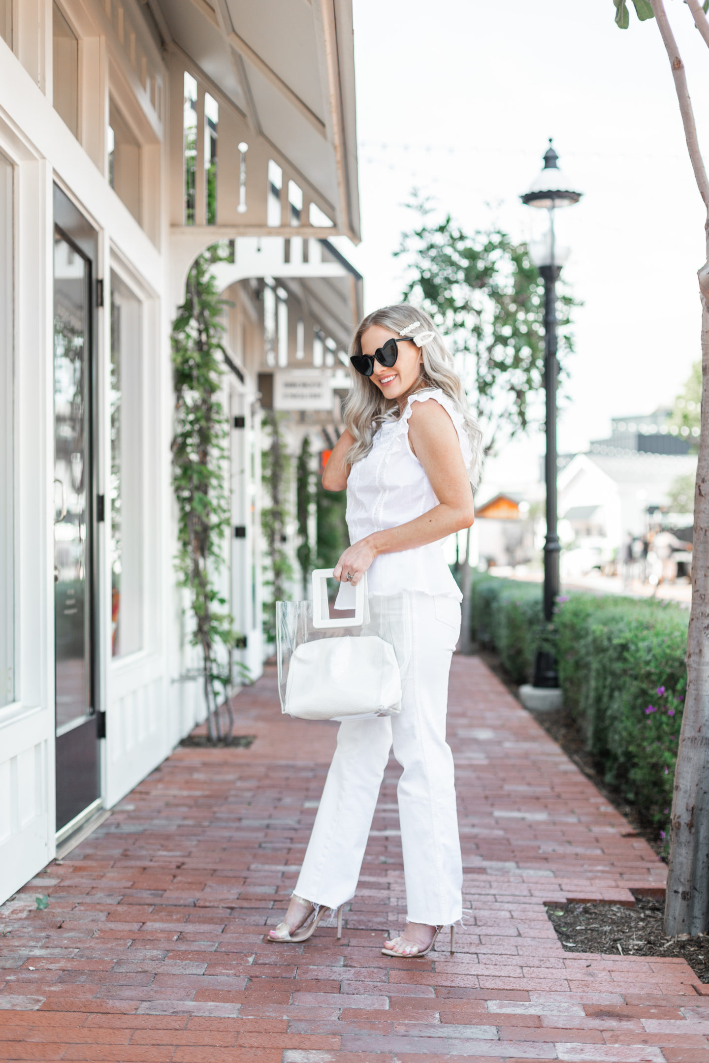How to Wear High Waisted White Jeans in Spring featured by top US fashion blog, Dress Me Blonde: image of a woman wearing Good American high waisted white jeans, Hunge lace peplum top, Tony Bianco sandals, Oweisong clear tote, pearl hair clips and Saint Laurent heart sunglasses
