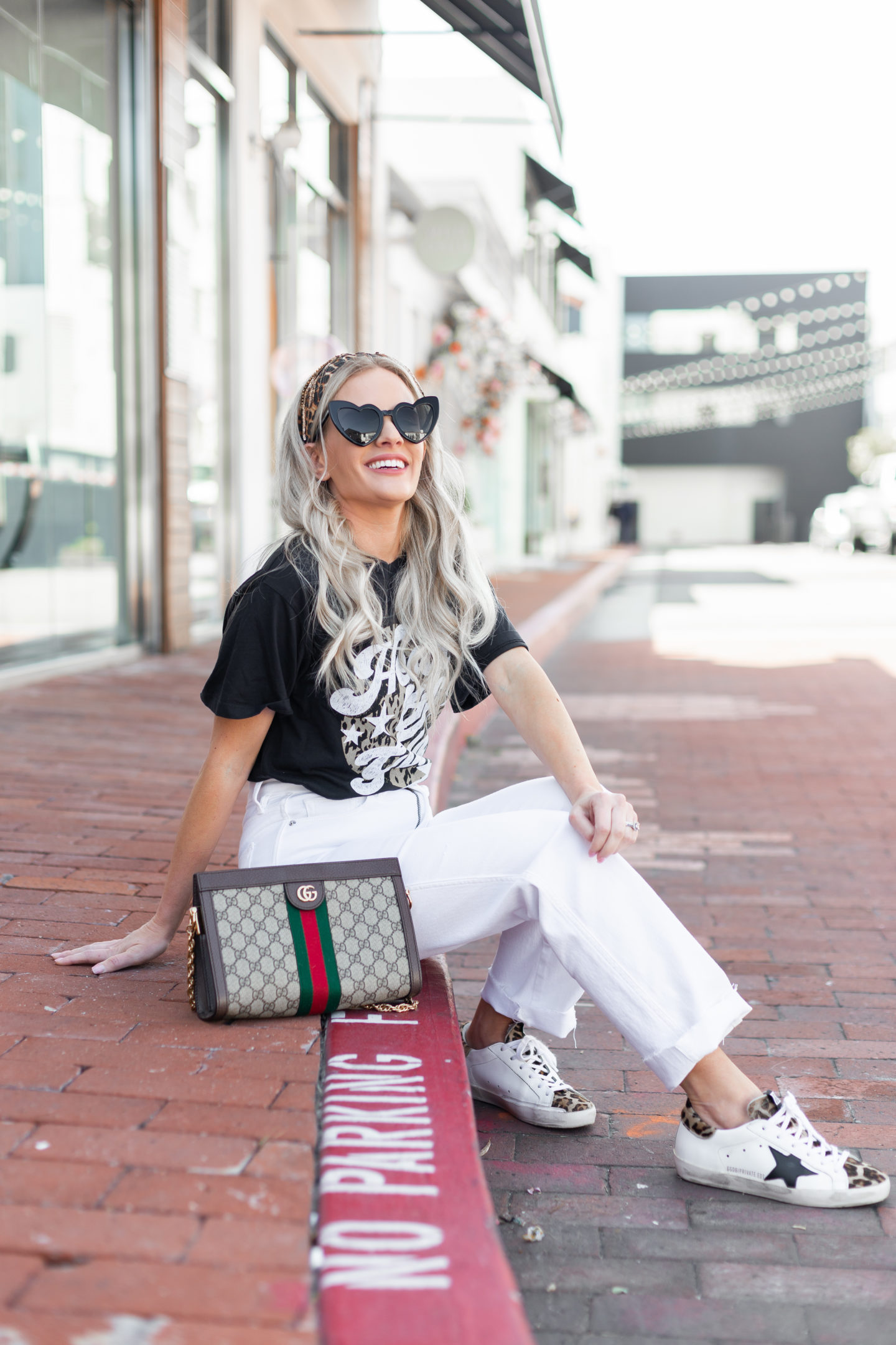 How to Wear High Waisted White Jeans in Spring featured by top US fashion blog, Dress Me Blonde: image of a woman wearing Good American high waisted white jeans, a Heart of Gold graphic tee, Golden Goose low top sneakers, Gucci small shoulder bag, leopard headband, and Saint Laurent heart sunglasses