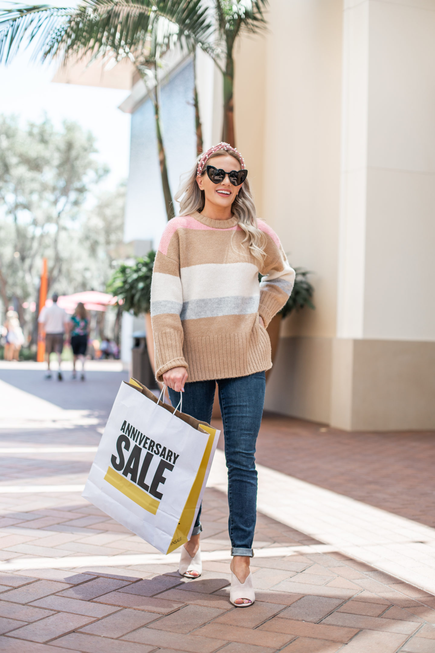 Nordstrom Anniversary Sale: Top Purchases featured by top US fashion blog, Dress Me Blonde: image of a woman walking outside while carrying a Nordstrom Anniversary Sale shopping bag and wearing a Topshop  Supersoft Stripe Crewneck Sweater, Good American Jeans, and BP. Mules.