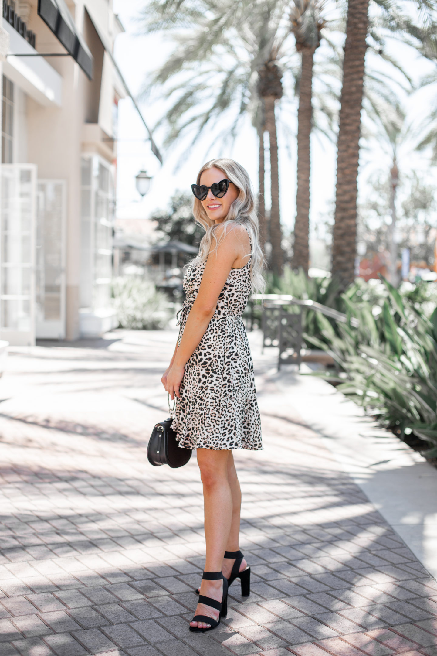 Nordstrom Anniversary Sale: Top Purchases featured by top US fashion blog, Dress Me Blonde: image of a woman standing outside and wearing a  Row A Cinch Front Leopard Mini Dress and Steve Madden Tiffani Ankle Strap Sandals.