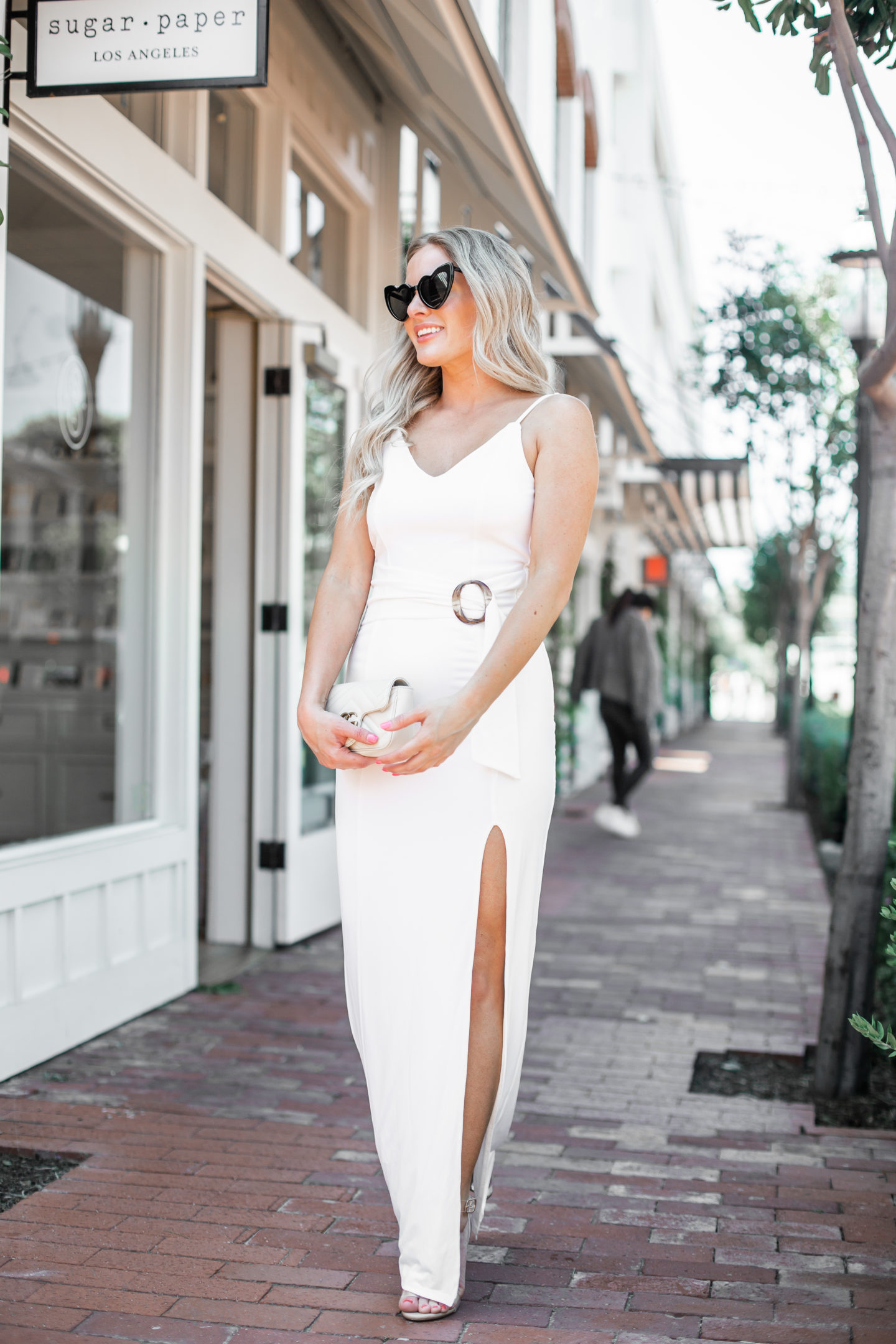 Cute end of summer date night outfit styled by top US fashion blog, Dress Me Blonde: image of a woman  wearing a white Tularosa Maxi Dress, Toni Bianco heels, GG Marmont Matelasse, Gucci barrettes, and Amazon love heart shaped sunglasses.