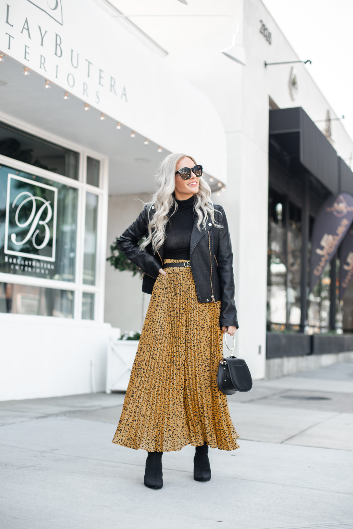 How to Style a Leopard Maxi Dress in the Fall, tips featured by top US fashion blog, Dress Me Blonde: image of a woman wearing an AFRM leopard maxi dress, BLANKNYC Moto jacket, Marc Fisher booties, Double GG Gucci belt, Yoome circular ring handbag, and a Leith black bodysuit.