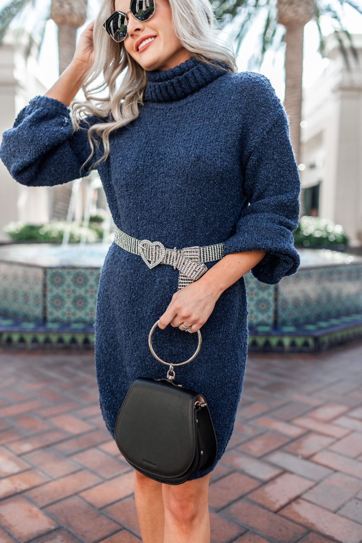 How to dress up a cozy sweater dress, tips featured by top US fashion blog, Dress Me Blonde: image of a woman wearing a Tularosa cozy sweater dress, GRLFRND belt, Jeffrey Campbell sock booties and a Whole bracelet bag.
